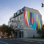 A tall building with a colorful mural of geometric triangles painted on the side.