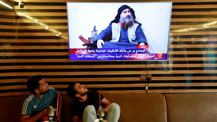 Two Iraqi youths stare at a TV showing an image of Abu Bakr al-Baghdadi.