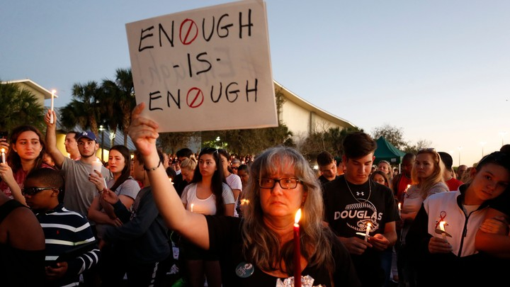 """People hold candles at a rally and a woman holds a sign that reads """"Enough is enough."""""""