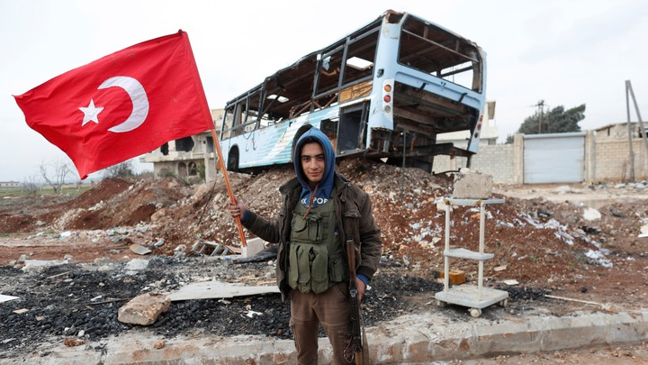 A Free Syrian Army fighter stands in front of a destroyed bus, holding a gun in one hand and a Turkish flag in the other.