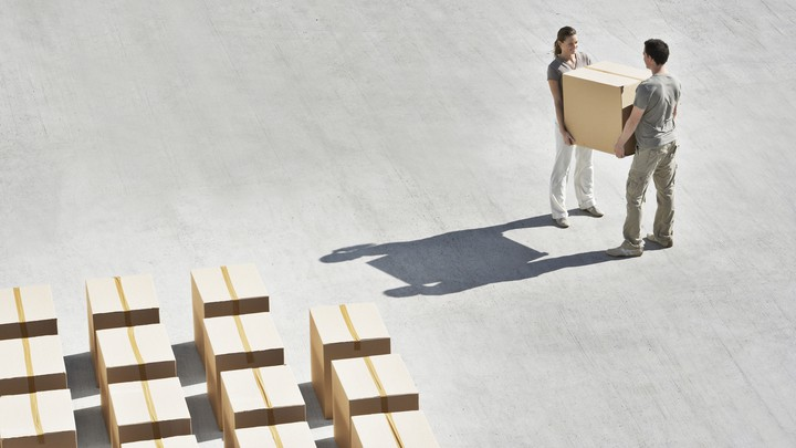 A man and a woman carrying a box together.