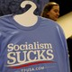 """A T-shirt on a hanger reads """"Socialism Sucks""""; two young women stand behind it."""