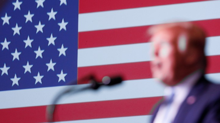 Donald Trump in front of an American flag.