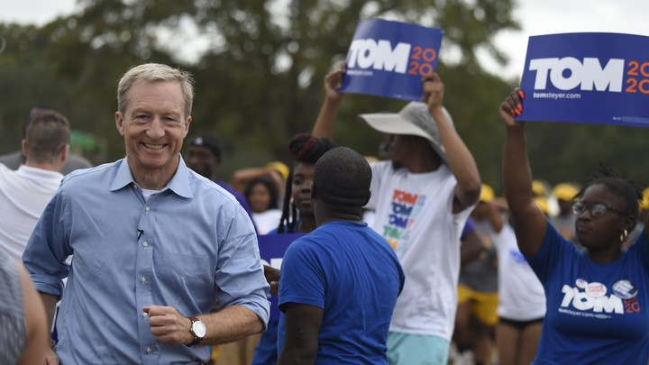 "Tom Steyer arrives at the Charleston Blue Jamboree. He's flanked by supporters holding ""Tom 2020"" signs."
