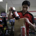 A 7-Eleven employee puts a bottle into a paper bag.
