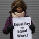 "A woman holds a sign saying ""Equal pay for equal work"""