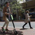 A man rides a motorized Lime scooter in San Francisco.