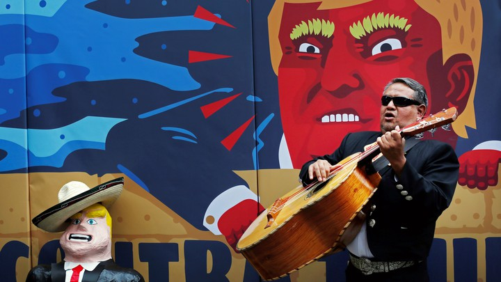 A member of the mariachi plays music next to a pinata depicting U.S. Republican presidential nominee Donald Trump in front of a wall with a caricature of him during a campaign encouraging U.S. citizens in Mexico to register to vote against Trump, in Mexico City, Mexico September 25, 2016.