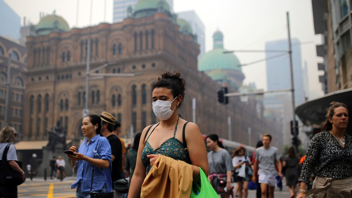 Pedestrians are seen wearing masks as smoke haze from bushfires in New South Wales blankets the central business district in Sydney.