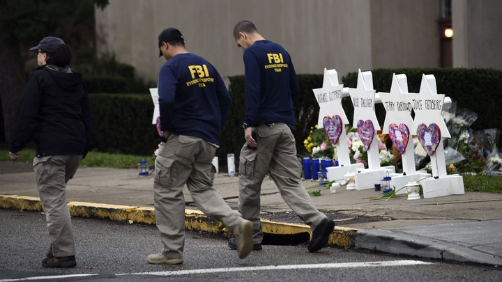 FBI officers walk past a memorial outside the Tree of Life synagogue in Pittsburgh.