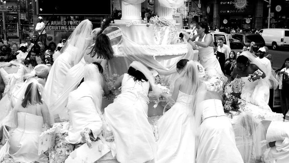 A black-and-white image of brides in wedding dresses scrambling onto a large structural wedding display