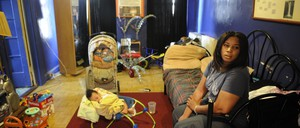 Michelle Echevarria sits with her baby in their Bronx apartment, which has a severe mold problem.