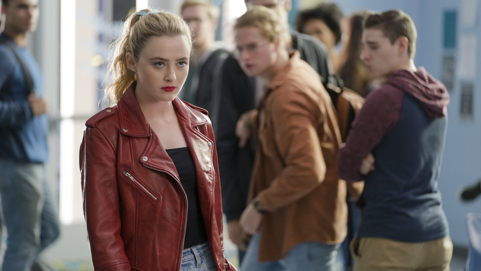 A young woman, played by actor Kathryn Newton, in a red leather jacket