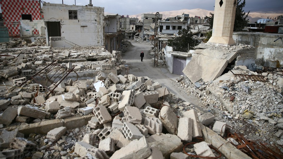 A man walks past damaged buildings in the rebel-held besieged city of Douma.