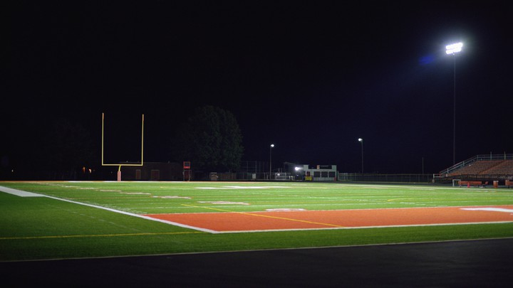 An empty football field at night.