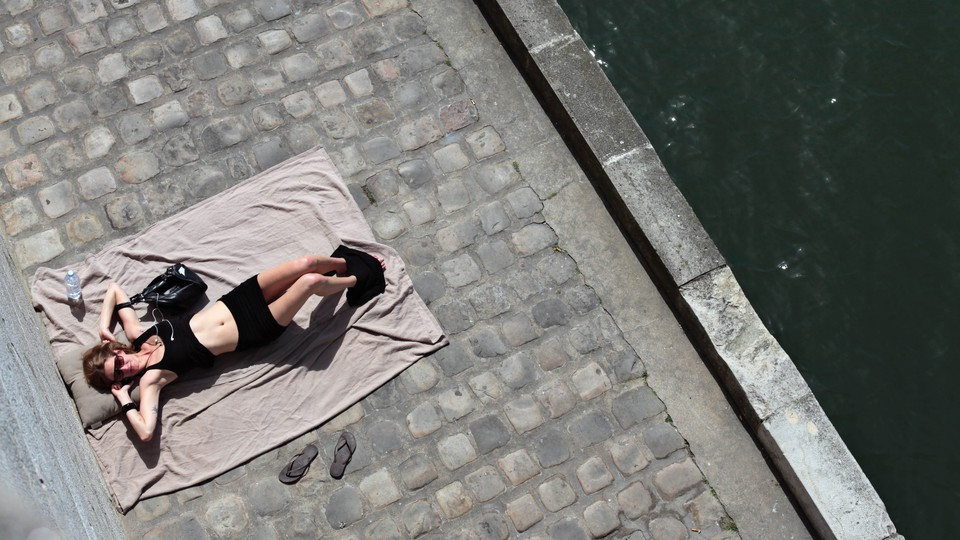 A woman sunbathes next to the Seine river in Paris, France.
