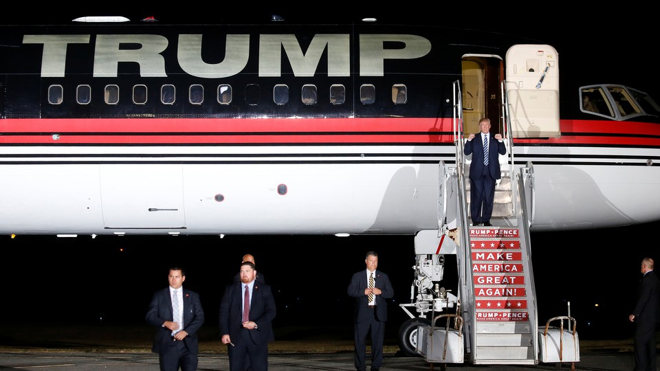 Donald Trump exiting a personal jet printed with his name