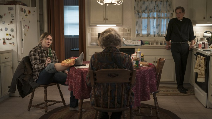 "Characters from the HBO show ""Mare of Easttown"" gathered around a kitchen table"
