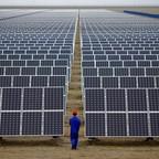A worker inspects solar panels northwest of Lanzhou, Gansu Province.