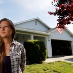 A woman stands in front of a house.