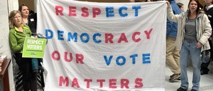 "Protestors hold a sign that reads ""Respect Democracy Our Vote Matters"""
