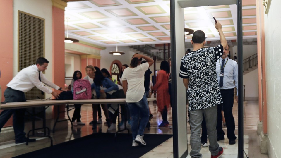 A student walks through a metal detector with his right arm in the air as other students collect their backpacks.