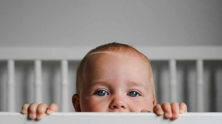 A baby peeks out of a crib.