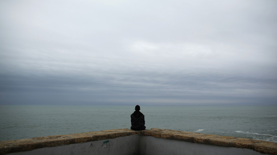 A person sitting on a low wall looking at the ocean under an overcast sky