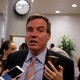 Mark Warner speaks as reporters hold up cellphones to record him.