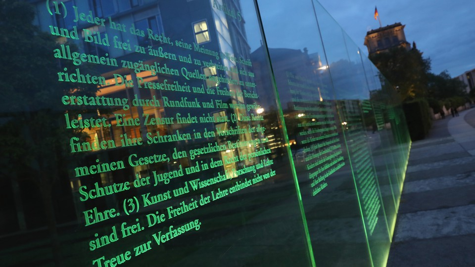 Articles of Germany's Basic Law (Grundgesetz), including article 5, which guarantees freedom of expression, the arts, and the press, stand illuminated on a glass wall in Berlin.