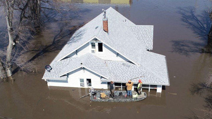 Muddy Paws Second Chance Rescue enters a flooded house to pull out several cats near Glenwood, Iowa, on March 18.