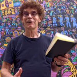 A curly haired artist reads from a book, in front of a mural he painted.