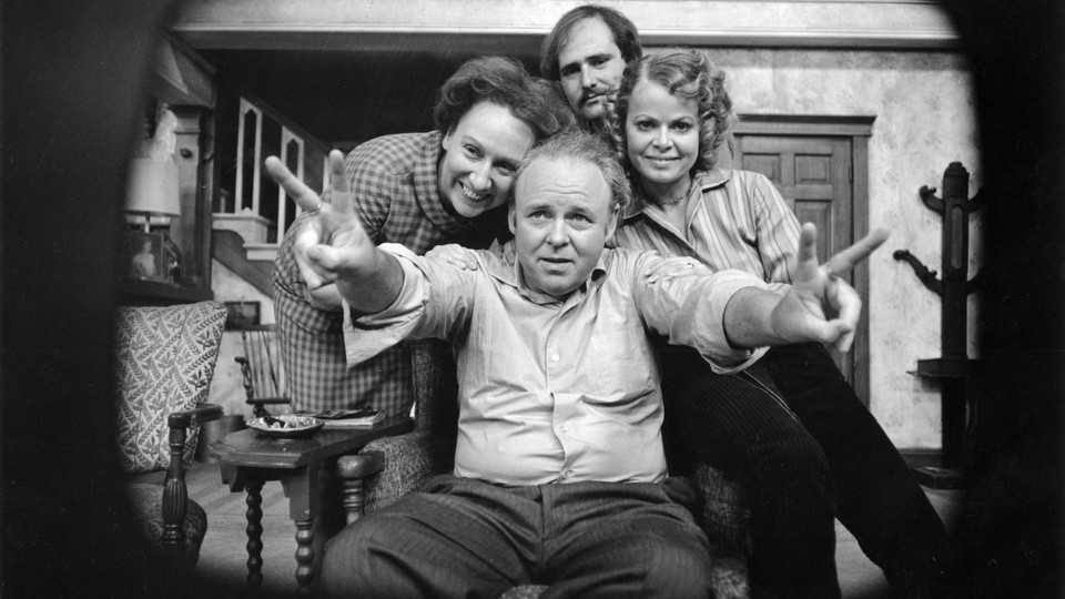 """A black-and-white photo shows the cast of """"All in the Family,"""" playing a set of parents, a daughter, and a son-in-law."""