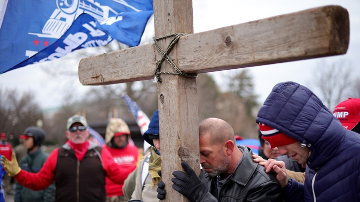 Supporters of President Donald Trump pray outside the U.S. Capitol on January 6, leaning on a large wooden cross.