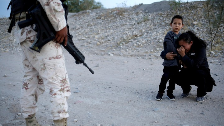 Guatemalan migrant Ledy Perez embraces her son Anthony on a dirt road as a member of the Mexican National Guard stands beside them.