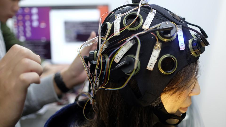 A woman wearing a brain-scanning helmet