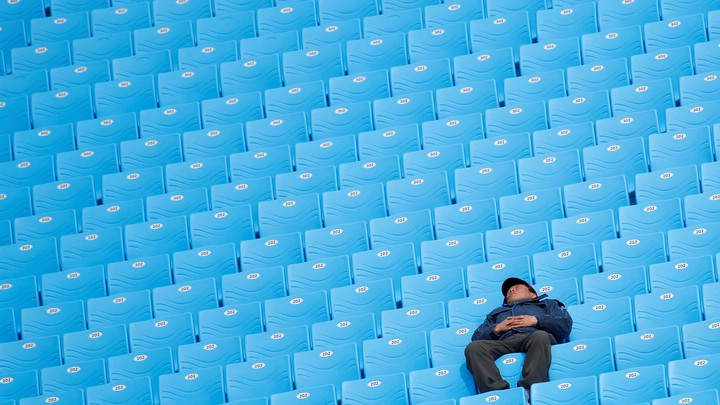 A man naps in a row of empty, bright-blue chairs.