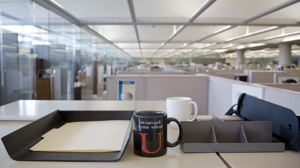"""A mug sits on a desk in an office. The mug reads """"We can't spell success without U."""""""