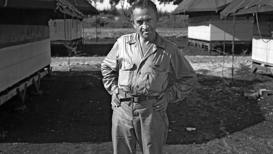"""William L. """"Atomic Bill"""" Laurence standing with hands on hips at Tinian Island in the Pacific, the launching point for the atomic bomb attacks against Hiroshima and Nagasaki"""