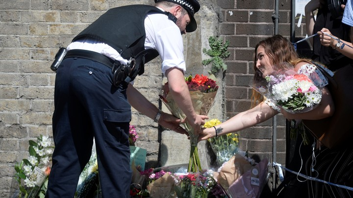 People leave flowers at a makeshift memorial where a man drove a van into Muslims outside a mosque in London.