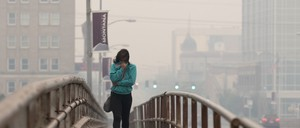 A woman covering her mouth with her jacket as she crosses a bridge in smoggy Missoula, Montana