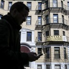 photo: a man with a smartphone in front of a rental apartment building in Boston.