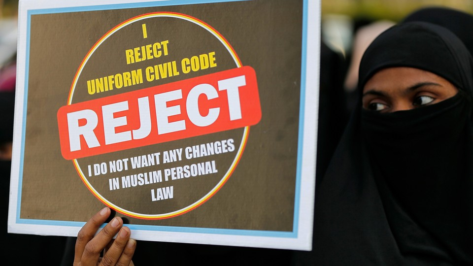 """A woman in a niqab holds a placard reading """"I reject uniform civil code. I do not want any changes in Muslim personal law."""""""