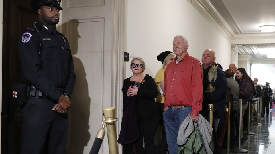 Members of the public wait in line hoping to get into the hearing room as former U.S. Ambassador to Ukraine Marie Yovanovitch arrives to testify.