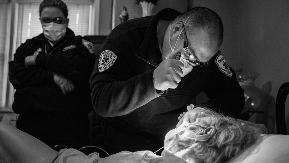 Medics assess a woman for Covid-19 symptoms before taking her to a hospital