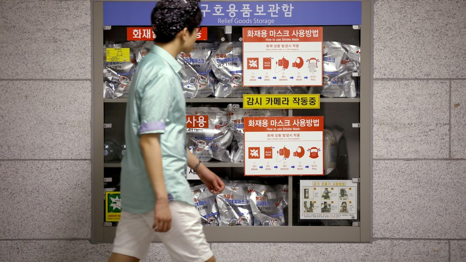 A young man walks in front of a relief goods storage inside of a subway in Seoul, South Korea.