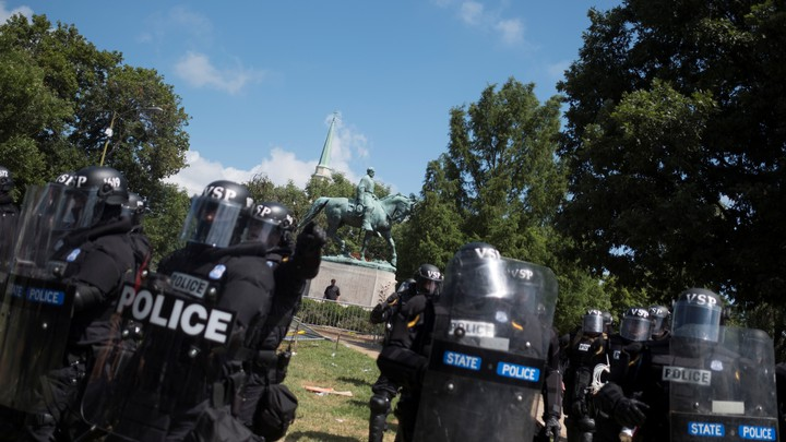 Riot police stand in formation in Charlottesville with a statue of Robert E. Lee behind them.