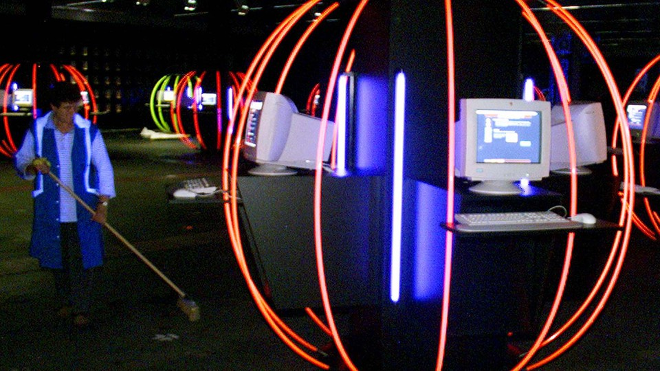 A person cleans up in a room full of computers and neon lights.