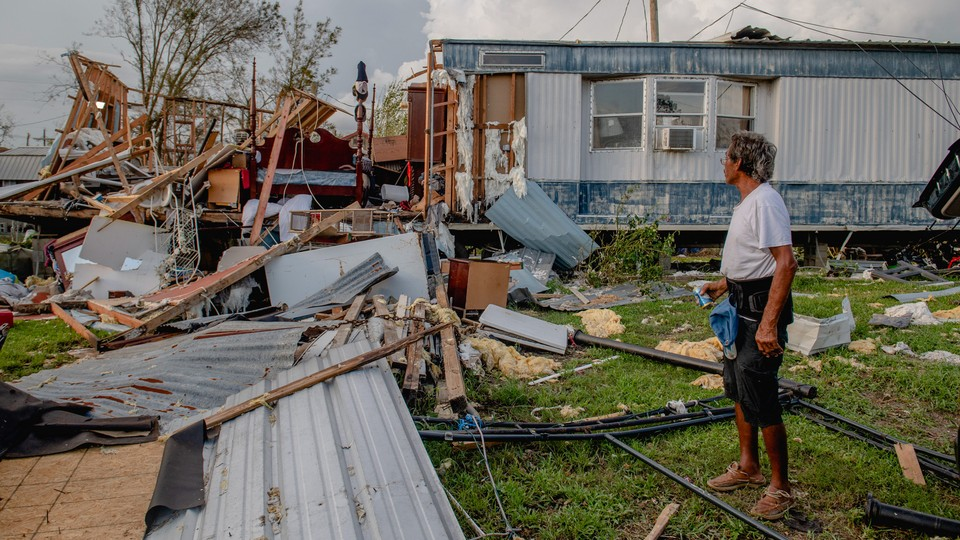 An image of a man in front of a damaged home after Hurricane Ida.