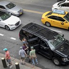 Traditional taxis vie for street space with ride-hailing vehicles from Uber and Lyft in New York City.